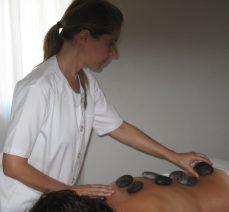 terapeuta corporal realizando masaje piedras calientes